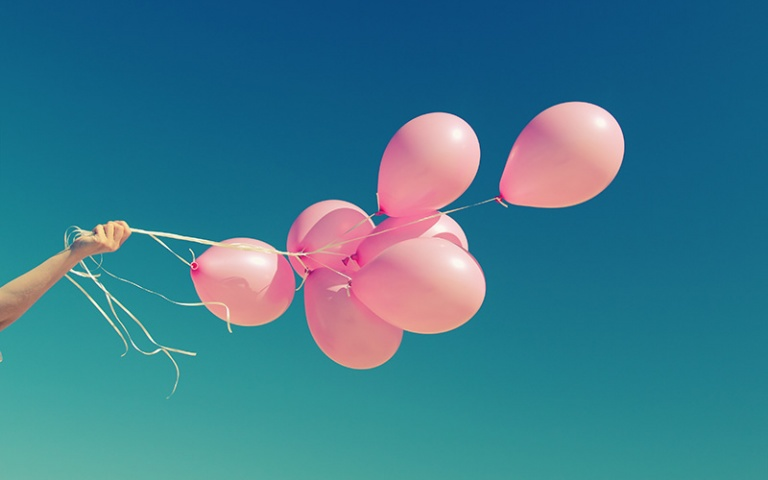 Pink balloons against a blue sky